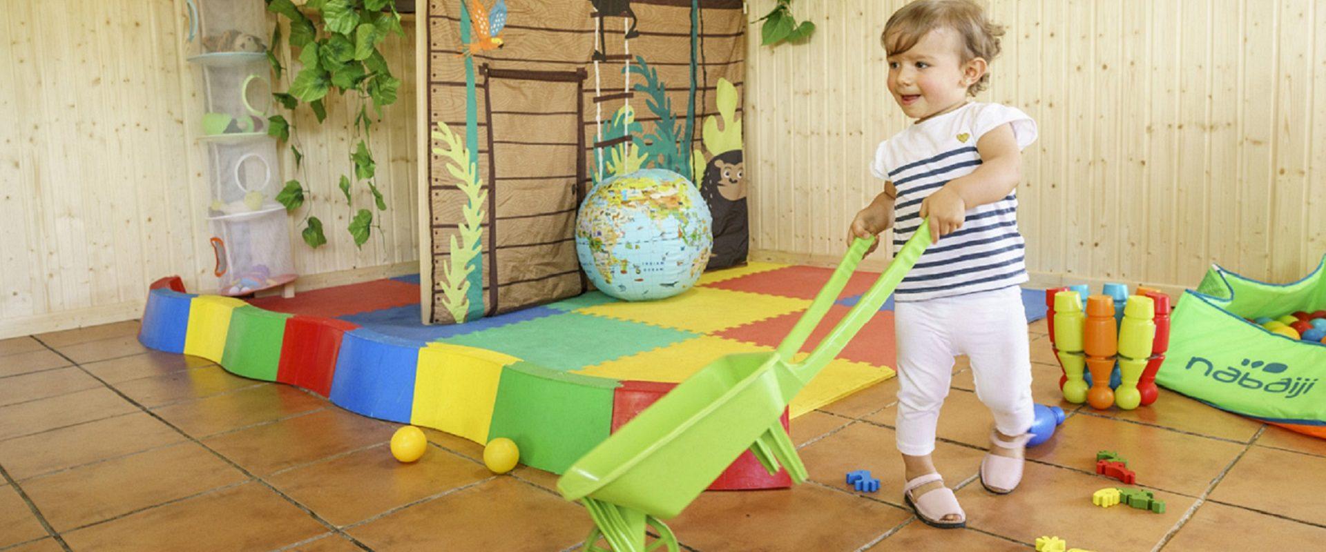 niño jugando con una carretilla en la ludoteca