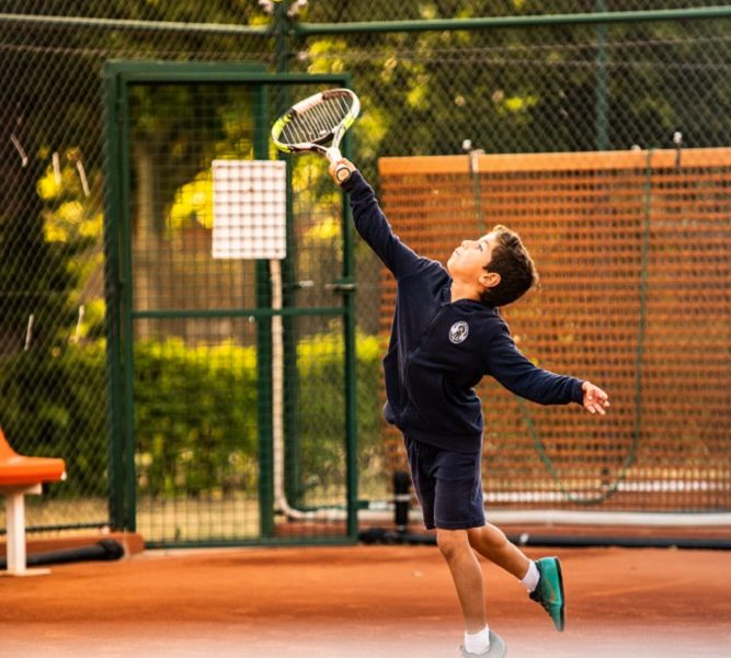 niño jugando al tenis en una pista de tierra batida