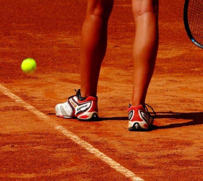 piernas de una jugadora de tenis en pista de tierra