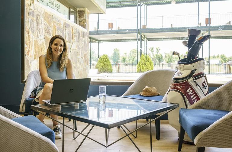 Mujer con ordenador y palos de golf en el salón social