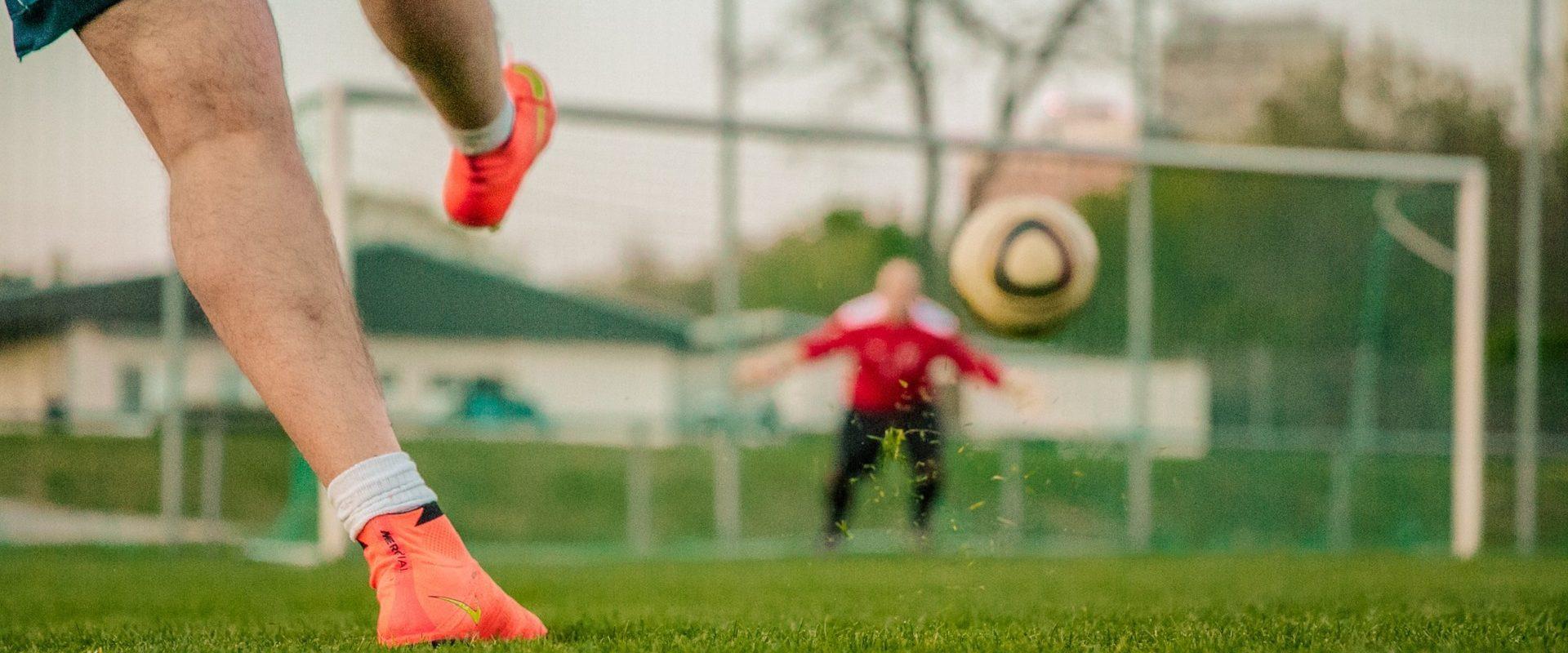 jugador chutando a portería de fútbol