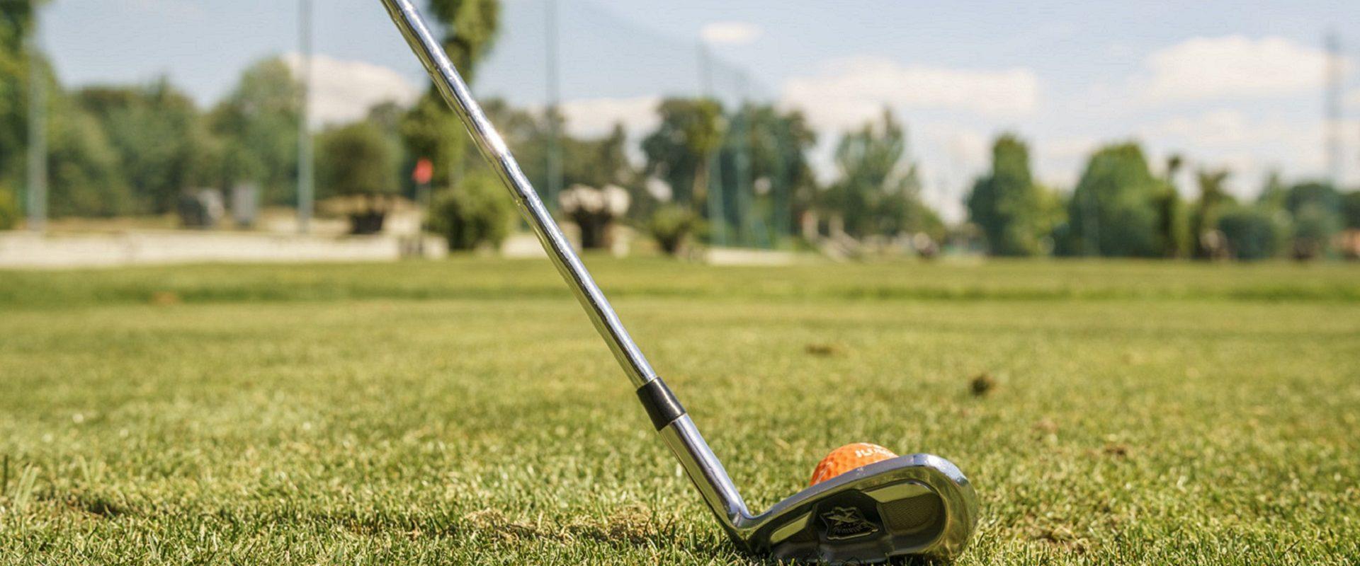 Palo y pelota de golf sobre cancha de golf