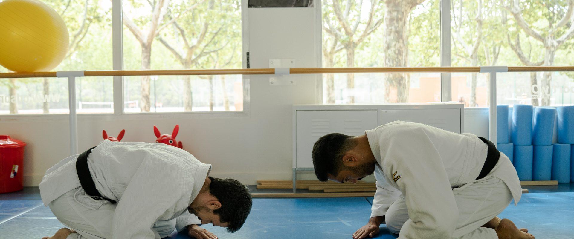 Dos personas realizan saludo de judo