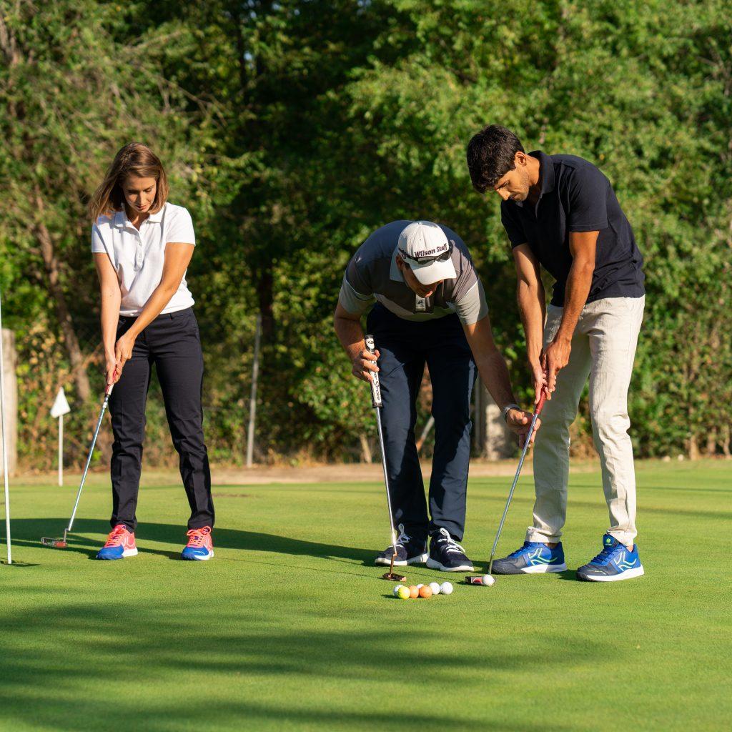 profesor de golf dando clase a dos alumnos