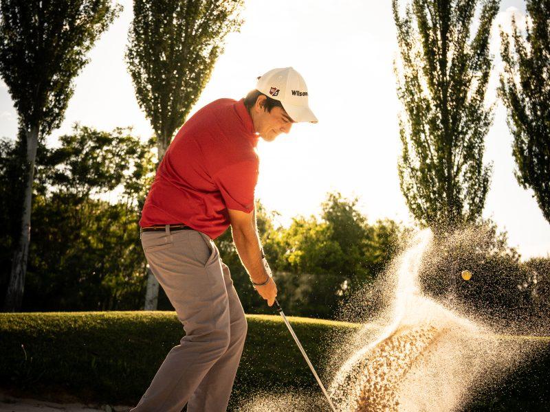Jugador de golf golpeando en el bunker