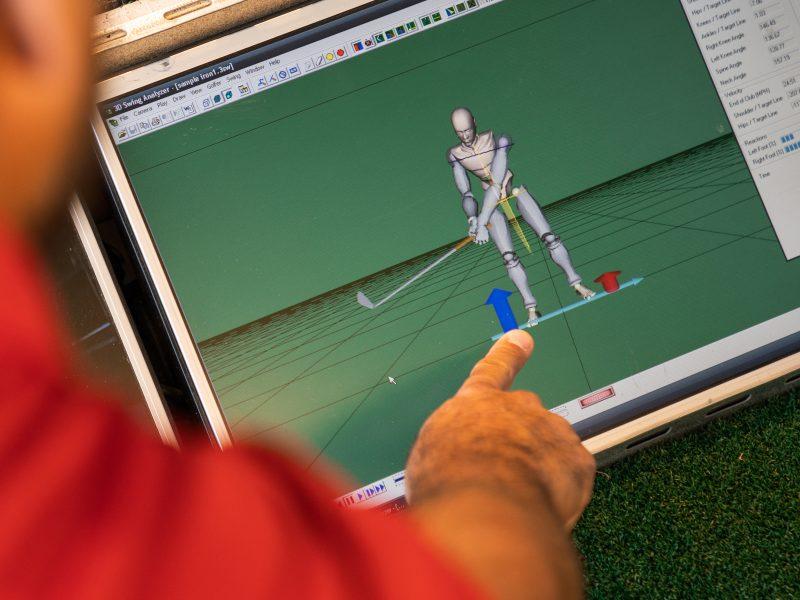 profesor de golf corrigiendo técnica en tablet