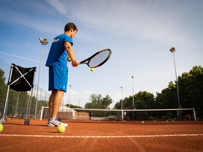 profesor de tenis dando clase en pista de tierra batida