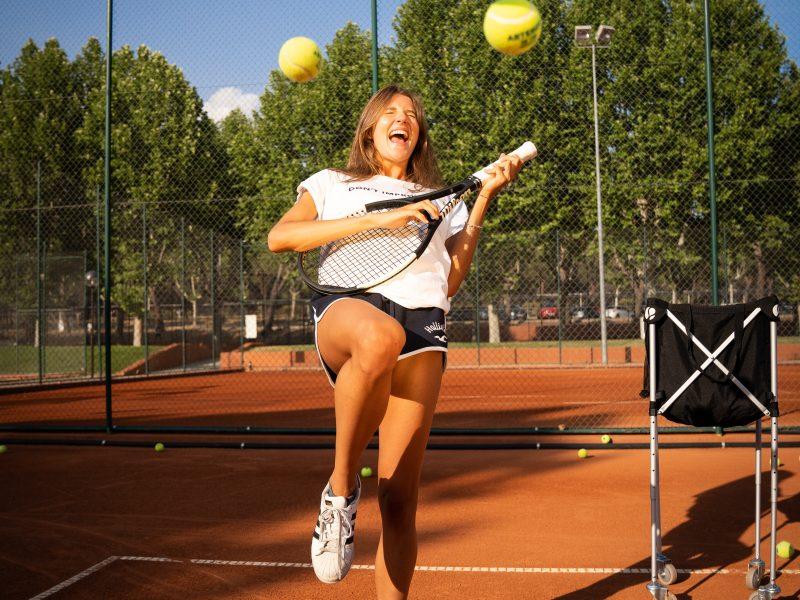 chica riéndose con raqueta de tenis a modo de guitarra y pelotas en el aire en pista de tierra batida