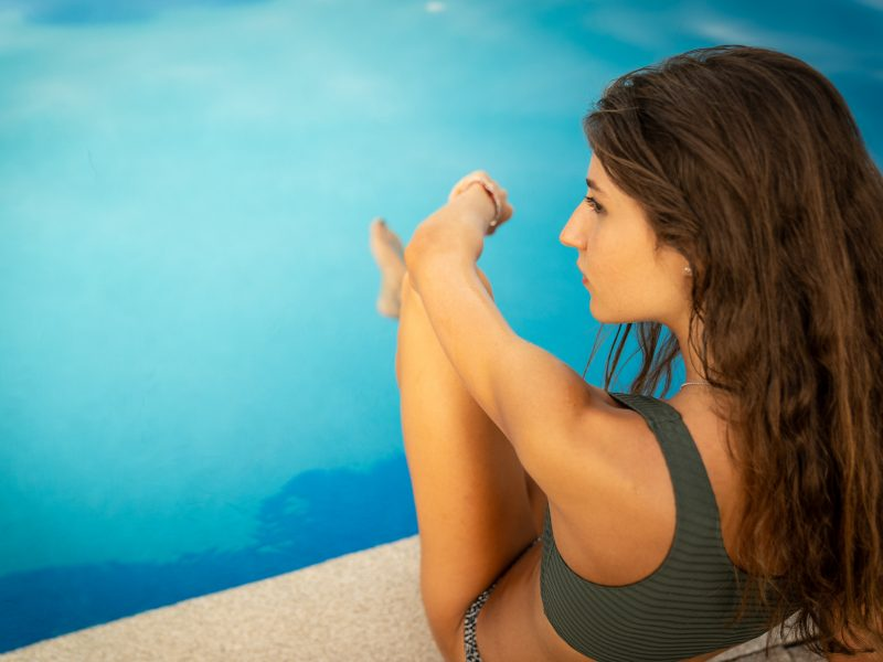 chica sentada al borde de la piscina