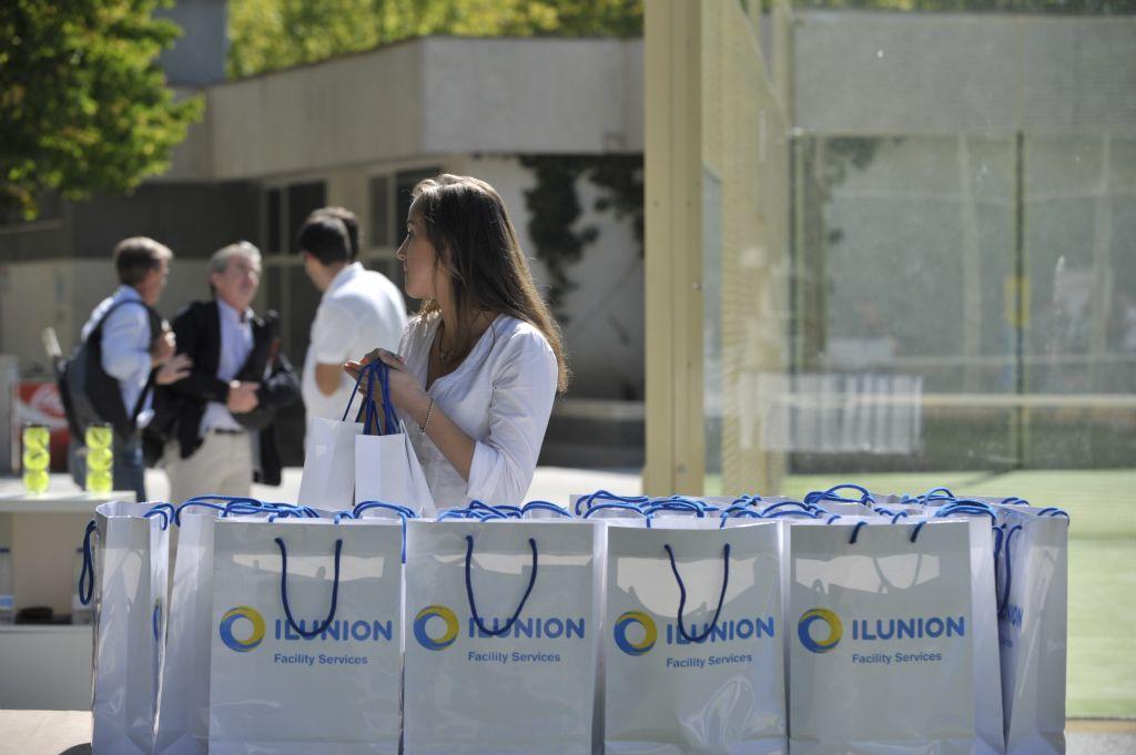 Azafata entregando bolsas de Ilunion junto a la pista central de padel