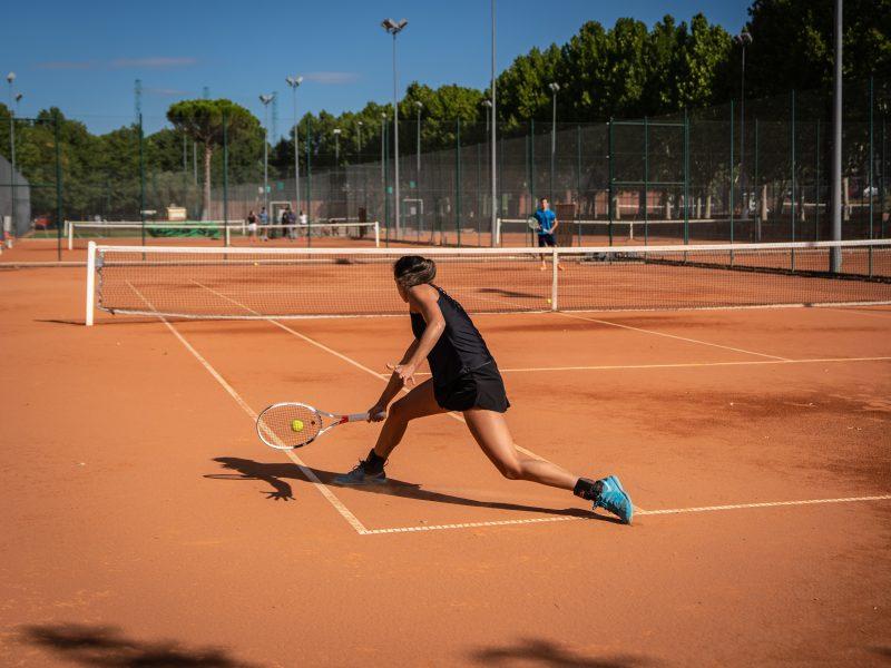 chica y chico jugando al tenis en pista de tierra batida