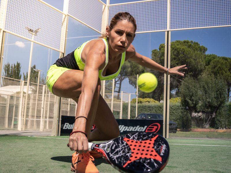Lorena Alonso voleando de revés en la pista central de padel