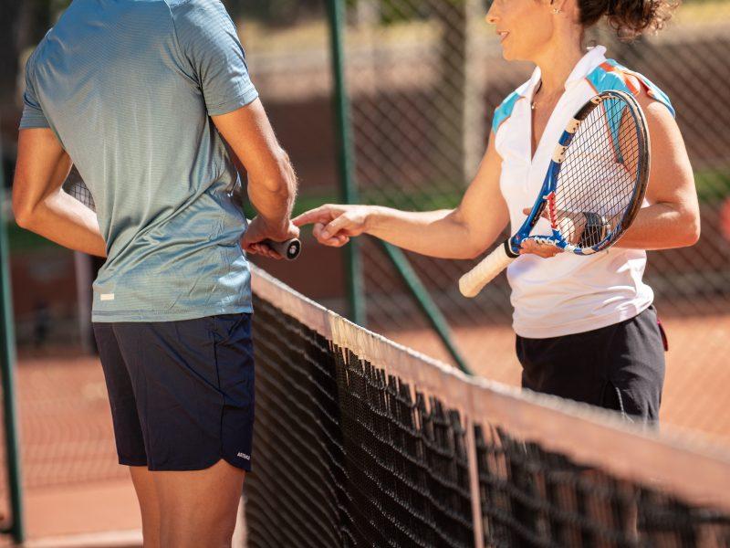 Virginia Ruano explicando a alumno en pista de tenis