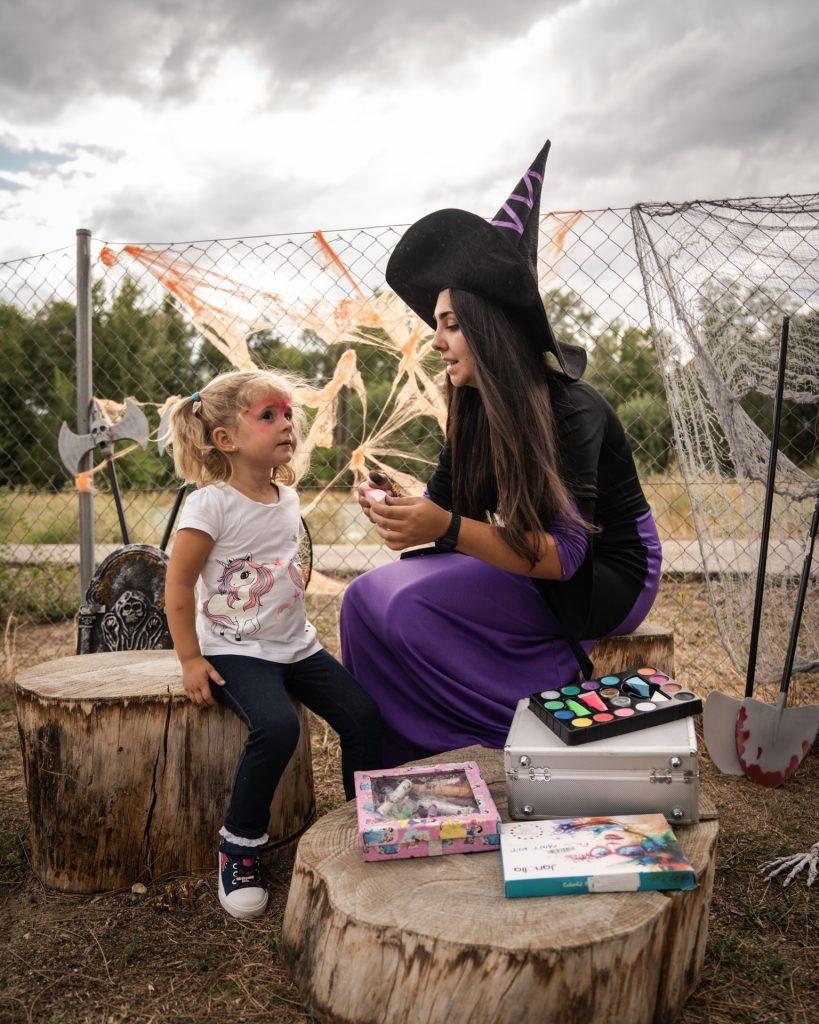 Monitora disfrazada de bruja con niña